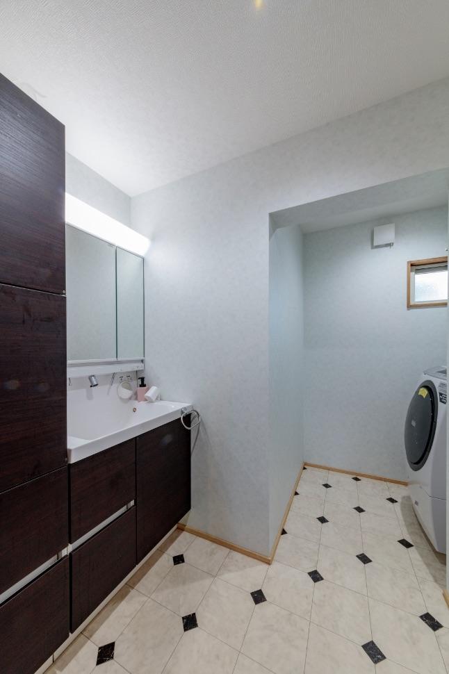 変形の空間をうまく活用した洗面室。床はタイル調のクッションフロアを選択。