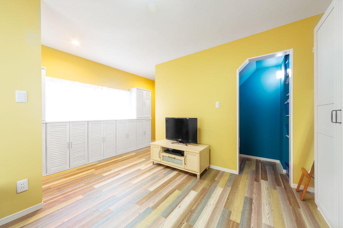 明るく楽しい雰囲気に生まれ変わったリビング兼寝室。階段下収納のブルーが良いアクセントに。