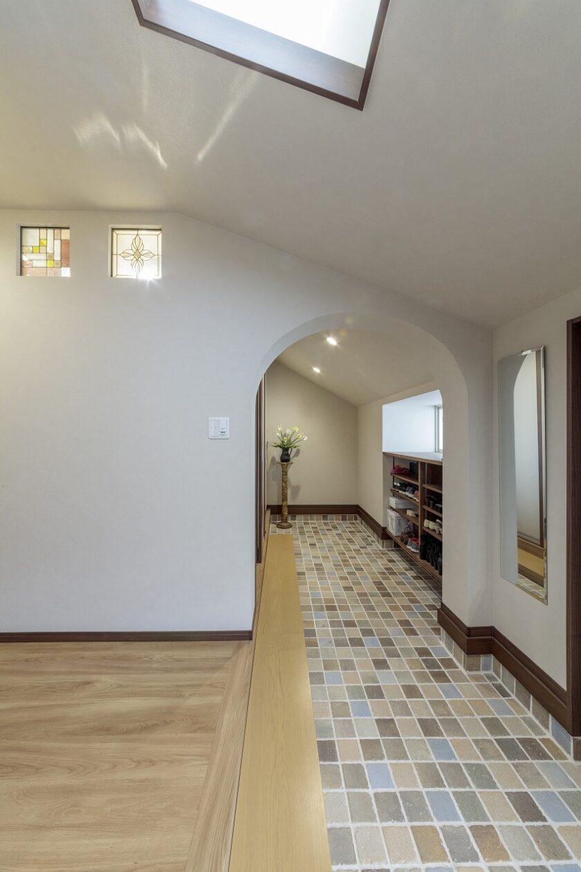 新たに設置した家族専用の玄関はキッチンと繋がっています。広い土間にこだわりのタイルを敷き、アールの垂れ壁で仕上げました。