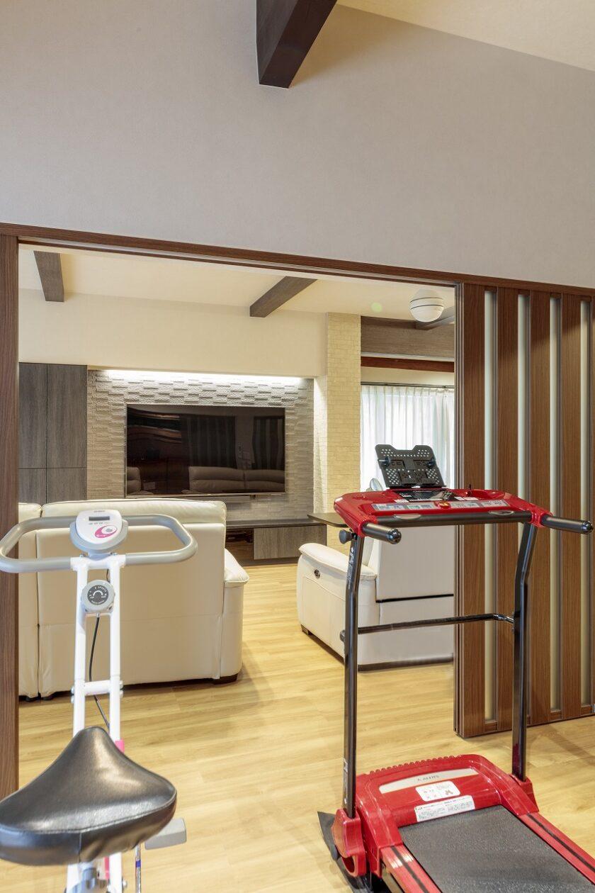 ファミリールームの半分はテレビを見ながらトレーニングできるフィットネススペース。間仕切りを吊り戸にしたことで床もすっきり。