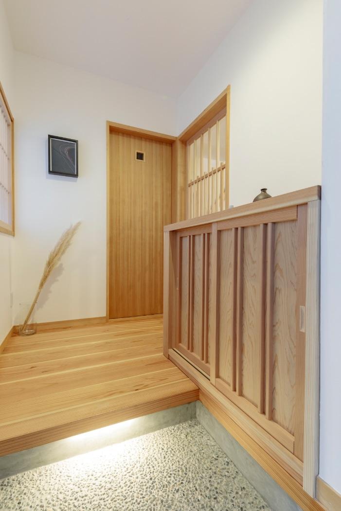 洗い出しの土間、漆喰の壁、杉材の床など和の素材と建築化照明でモダンなテイストにまとめた玄関。