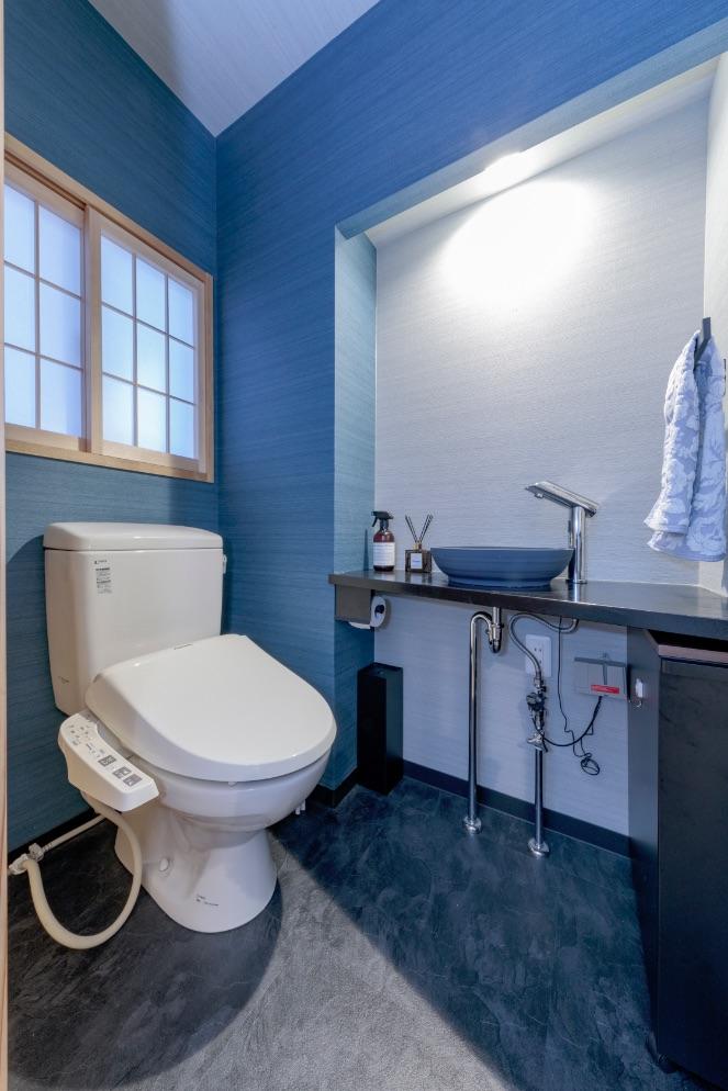 黒の石目調の床にブルーのクロス、明かりはニッチ部分の間接照明に。小料理屋をイメージしたトイレ。