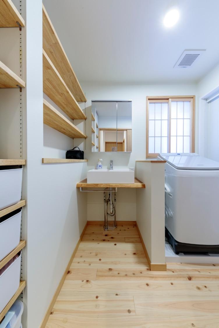 一枚板のカウンターと壁面の可動棚を造作した、シンプルで美しい洗面室。床はヒノキの無垢材を採用。
