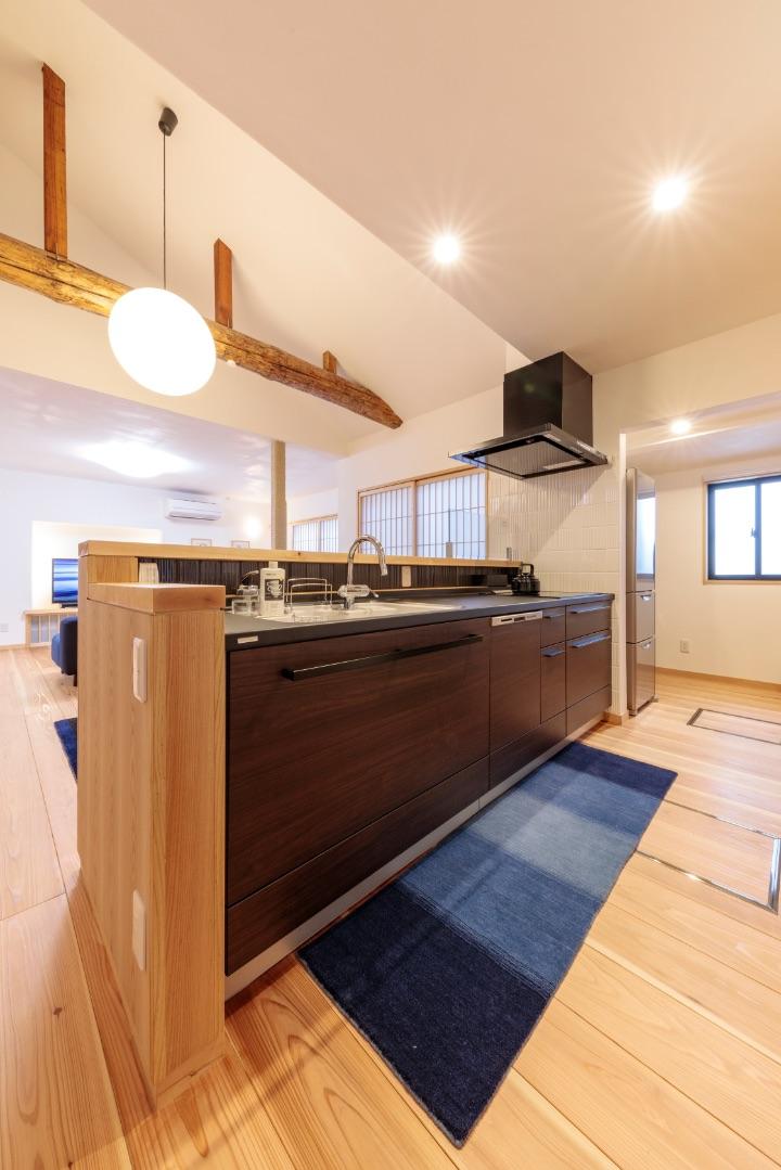 ダークカーラのシステムキッチンを無垢のカウンターと突板で家具のように仕上げました。