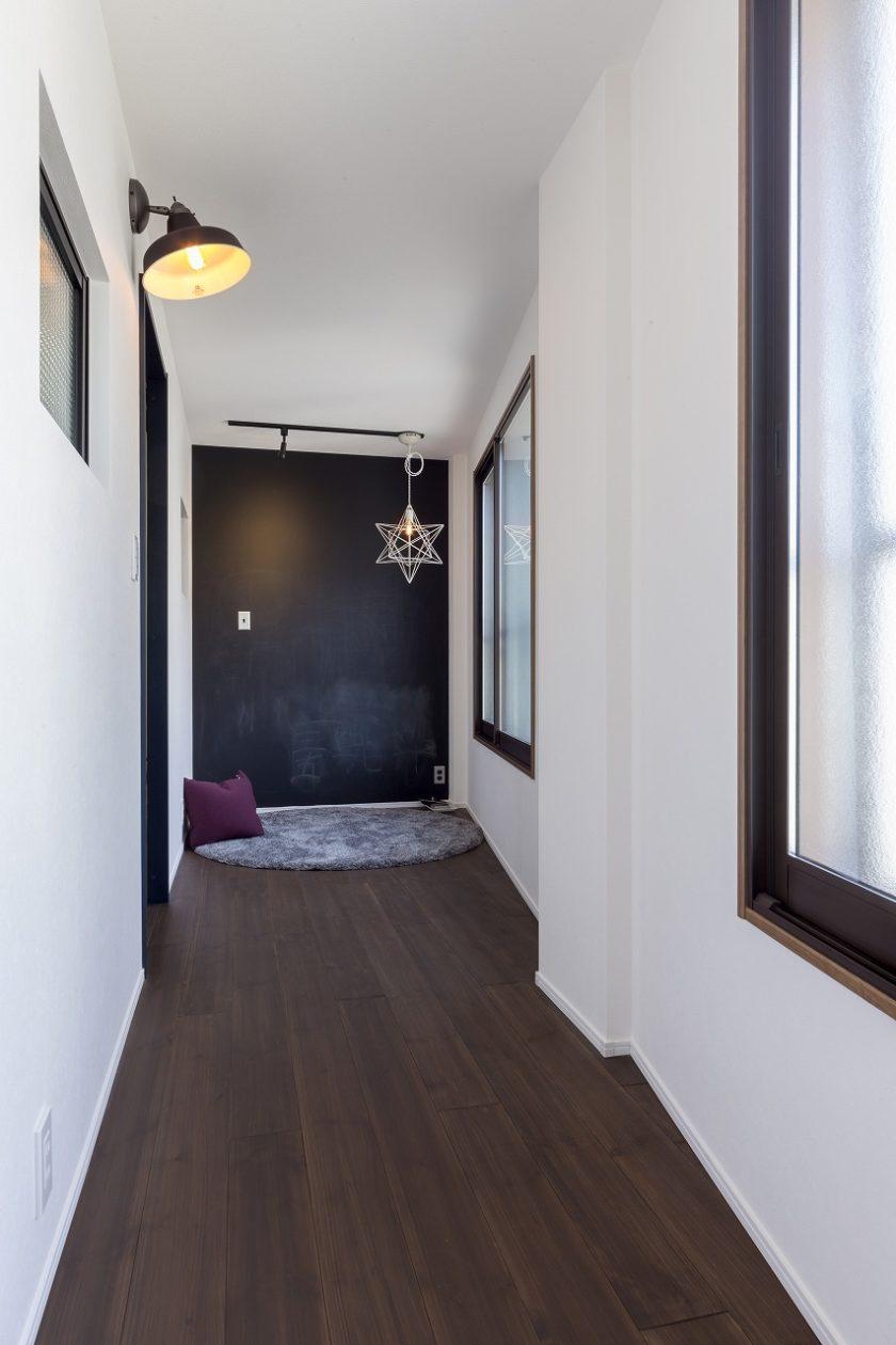2階廊下の突き当りはマグネットもつくスチールタイプの黒板。コンセントやスイッチにもこだわり。