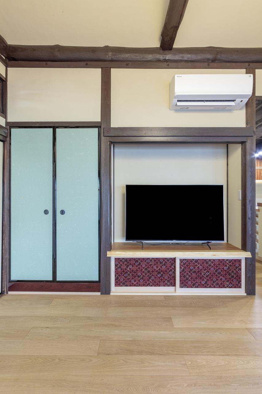 押入れだった空間をテレビ用のスペースに。一枚板のカウンター下の収納扉は着物の布を貼っています。