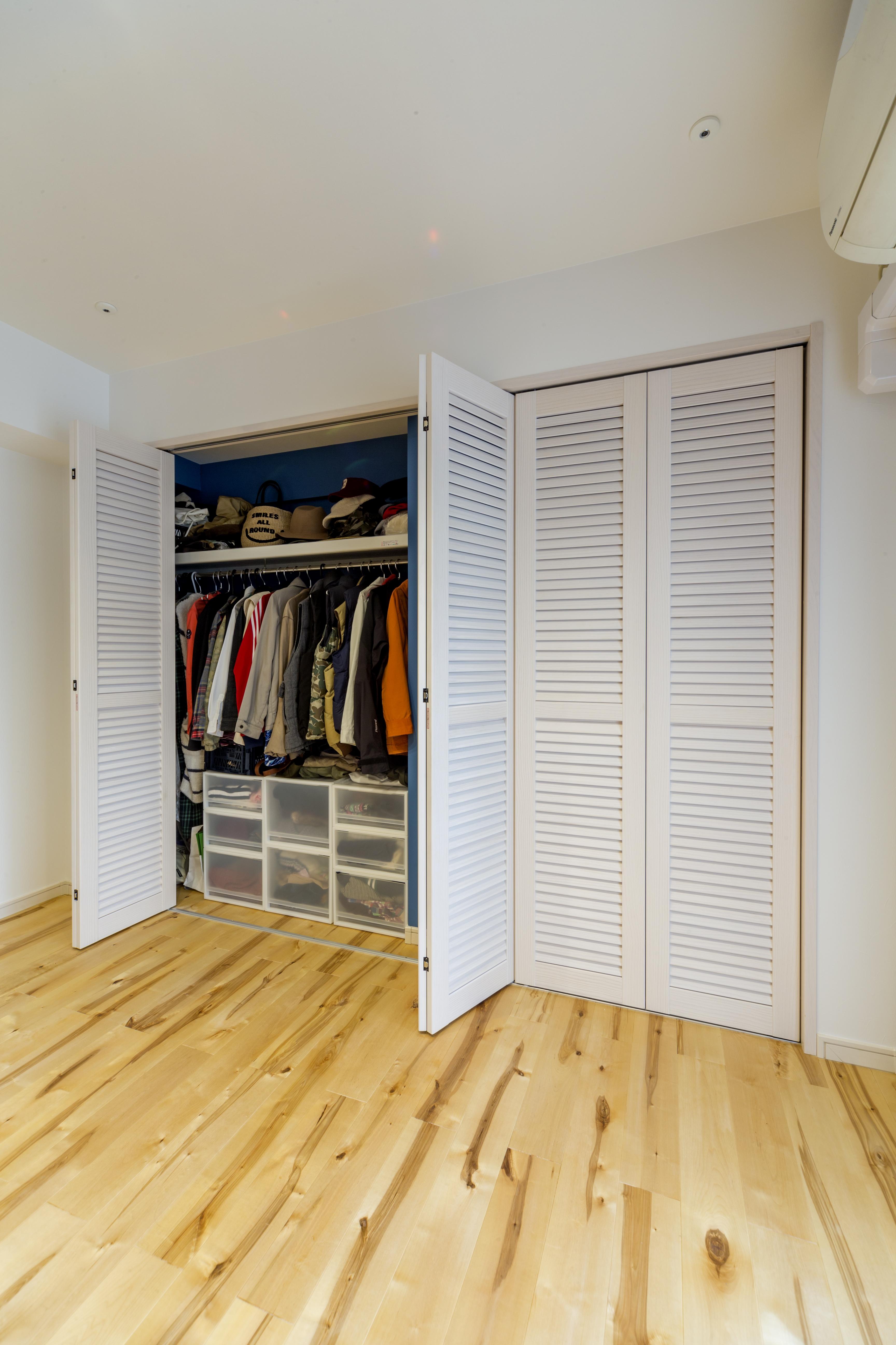 一辺の壁をクローゼットに、ルーバーの扉で圧迫感なくデザイン性も高く