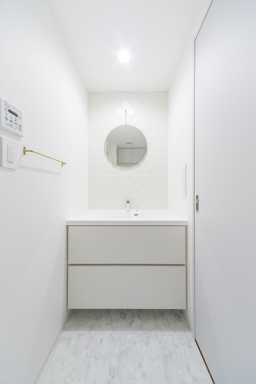 丸いタイルに丸い鏡、真鍮製のタオルハンガーなどこだわりを集めた造作の洗面室。