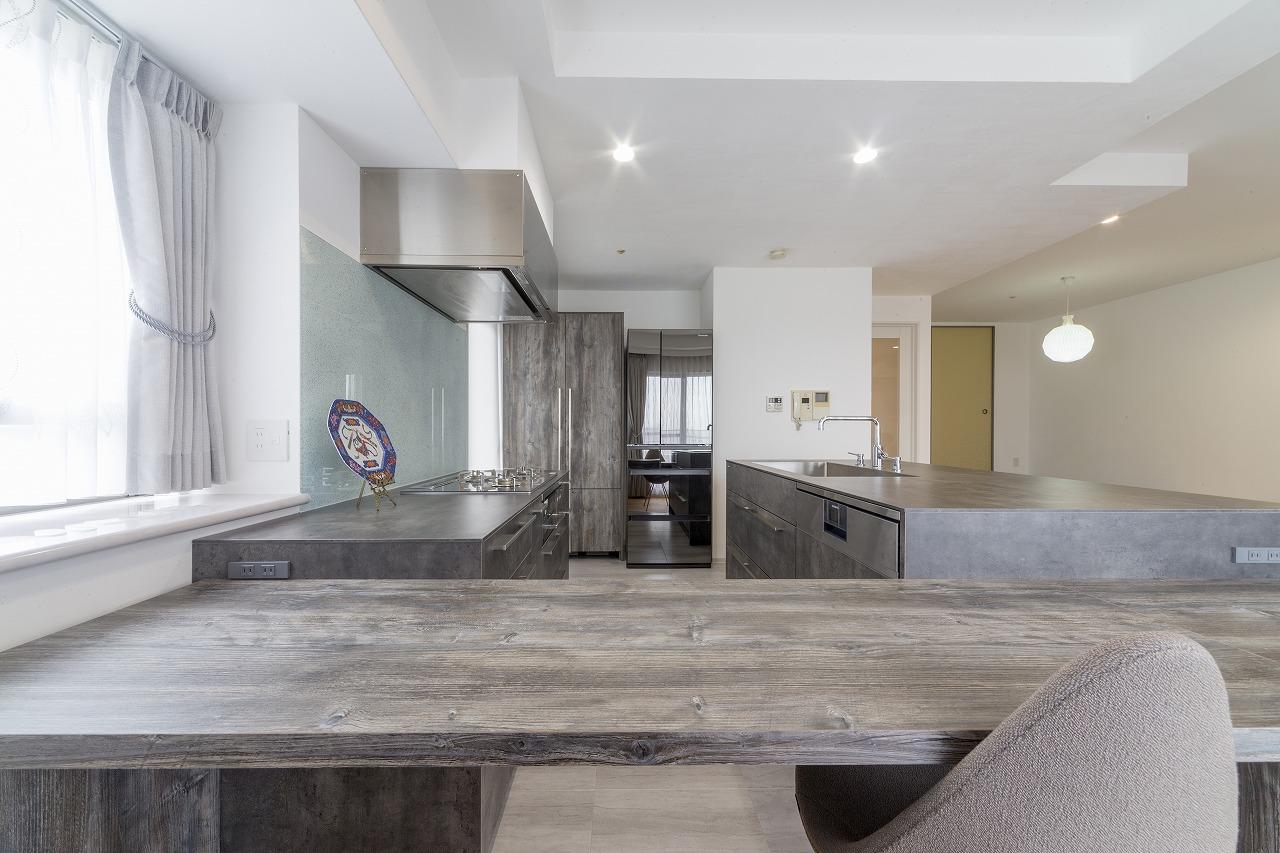 キッチンには石目調を、カウンターテーブルと冷蔵庫横のキャビネットには同じ色調の木目のデザインを選択。