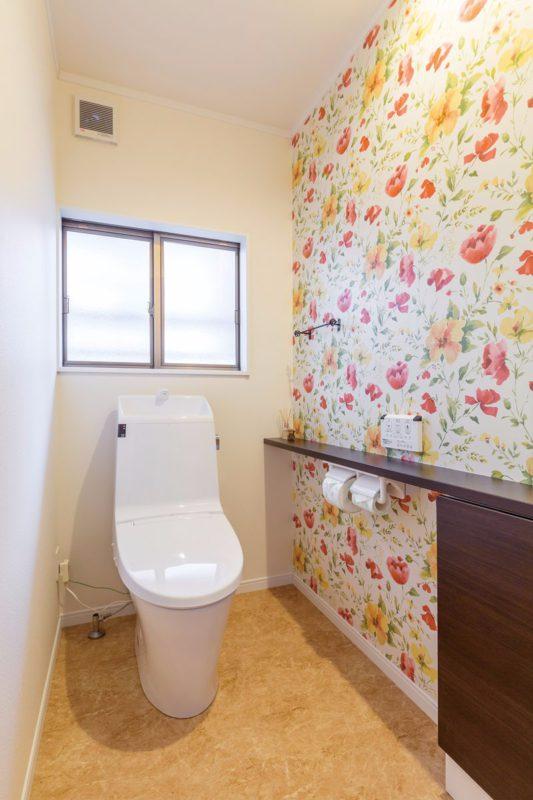 寝室からの移動も楽なトイレルーム。壁の片面に花柄のアクセントクロスを