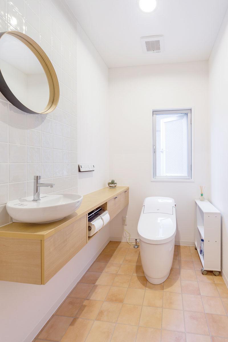奥さまが温めていた、タイル貼りの壁と丸い鏡をコーディネートした理想のトイレ