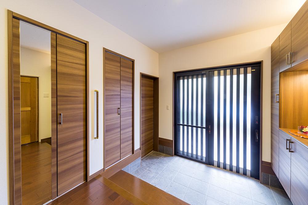 大型の鏡や建具が落ち着いた雰囲気になじむ、玄関ホール。