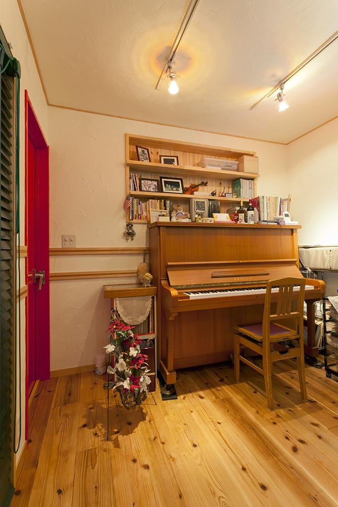 壁の厚みを利用したディスプレイ棚。床材は、木目のピアノとの相性も考えたスギ材に。