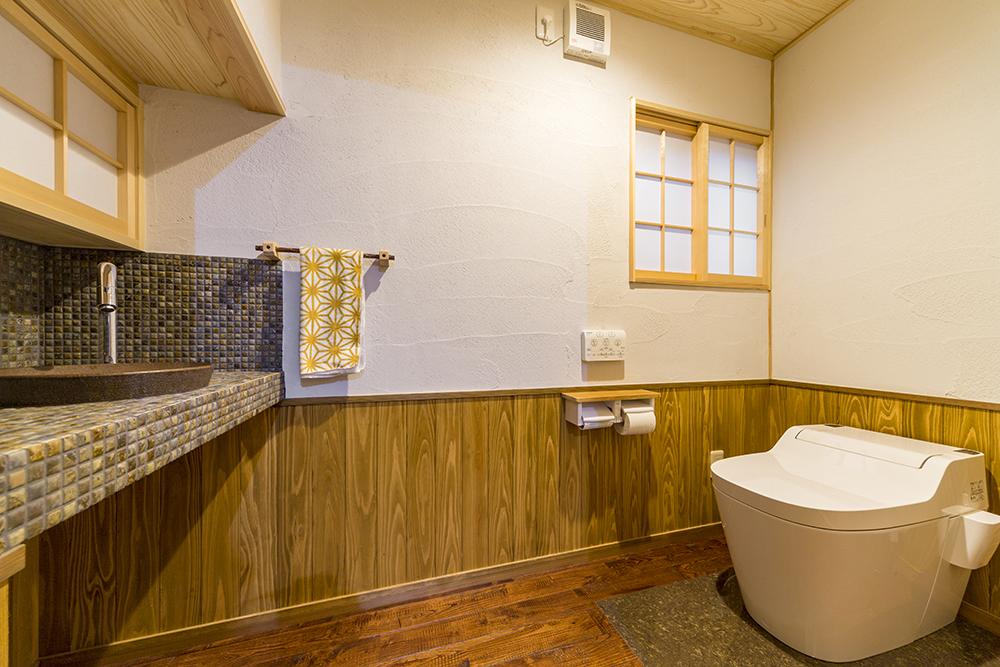 木目がやさしい落ち着きのトイレ。床は手入れしやすいよう一部タイルに。