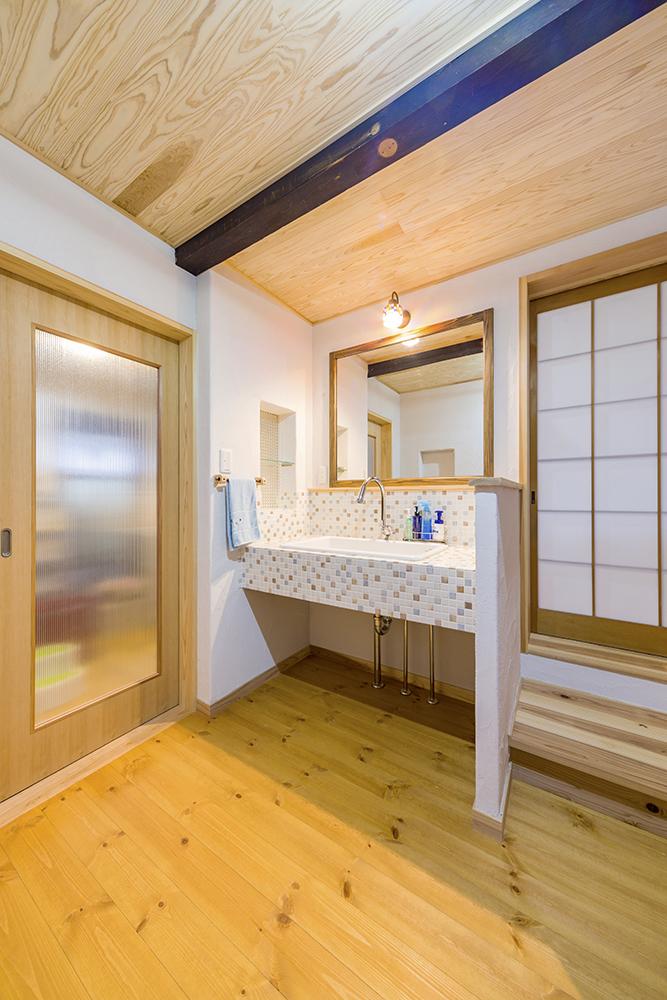 洗面所の広いボウルは実験室用のもの。家族が並んで歯磨きできる大きな鏡も造り付けました。