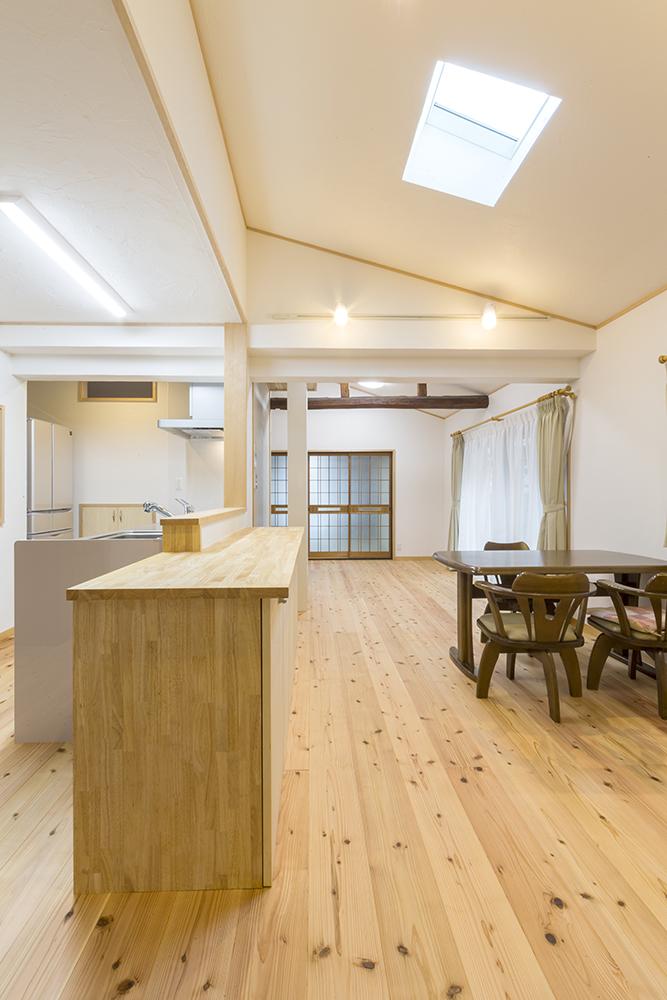 勾配天井が空間に広がりの視覚効果を持たせるLDK。やさしい木の色合い。