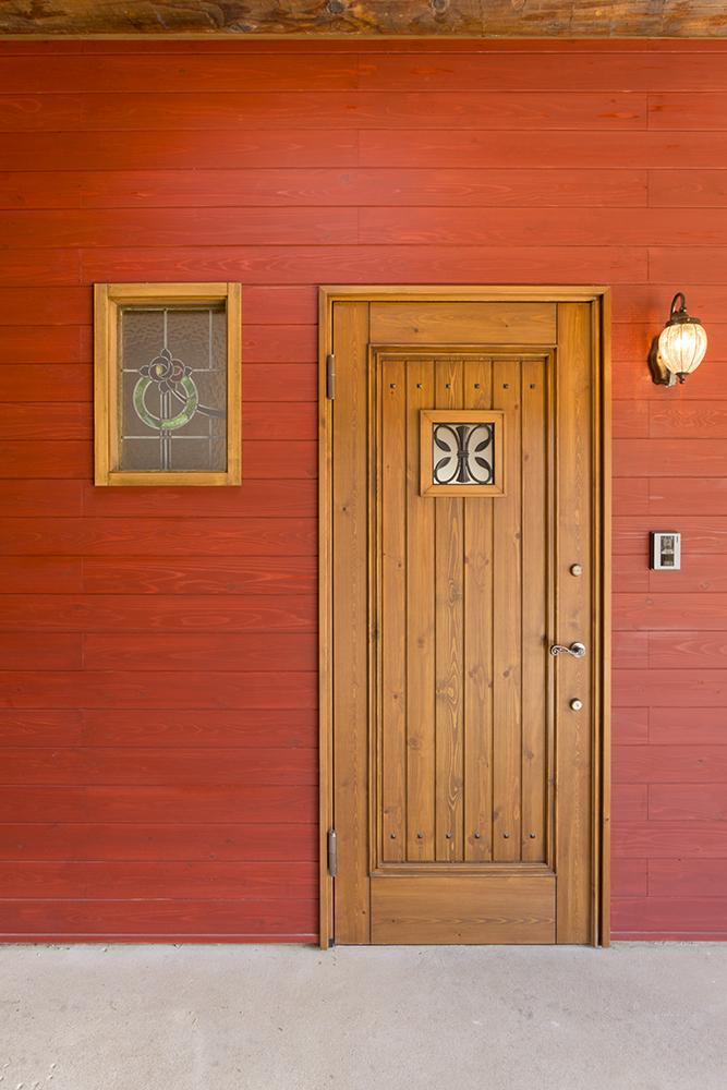 壁面の赤と絶妙なバランスの木製玄関戸。