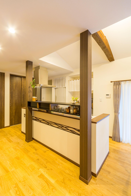 構造上必要なキッチン前の2本の柱を活用し、収納棚を設置するというアイディアが光ります。