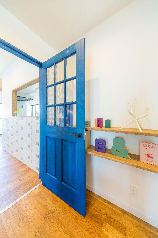 リビングへの扉は輸入建具を採用。鮮やかなブルーが心地よく空間を切り替えてくれます。