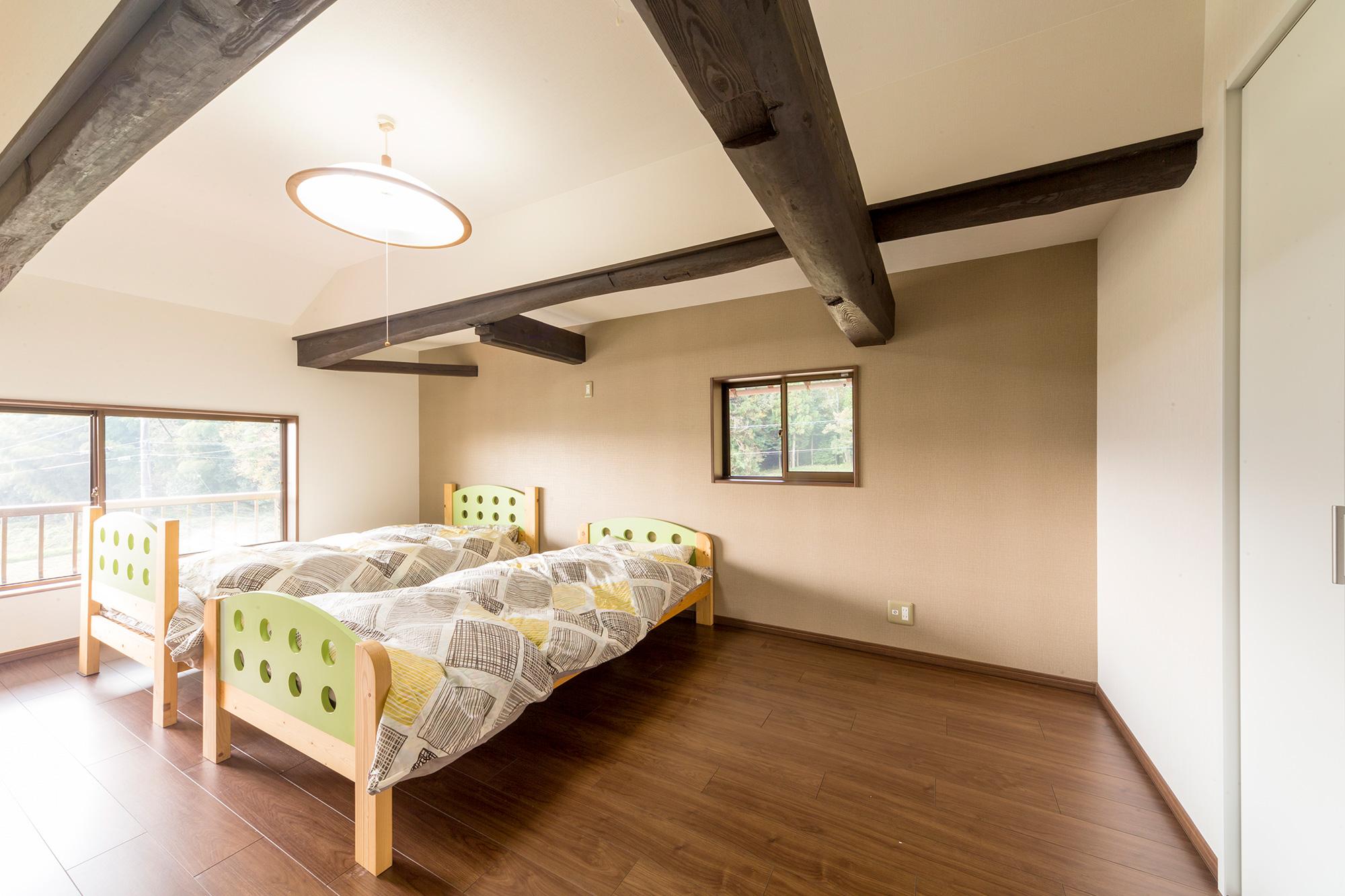 ご夫婦の寝室。勾配天井と手に届きそうな梁の効果で、包み込まれるような雰囲気も。
