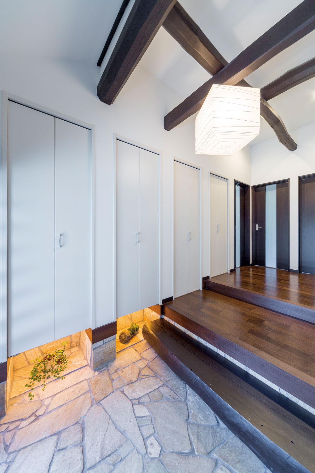 以前から使っていた玄関床や上がりの踏み台を活かした玄関。収納下にはスペースを設け間接照明で演出。