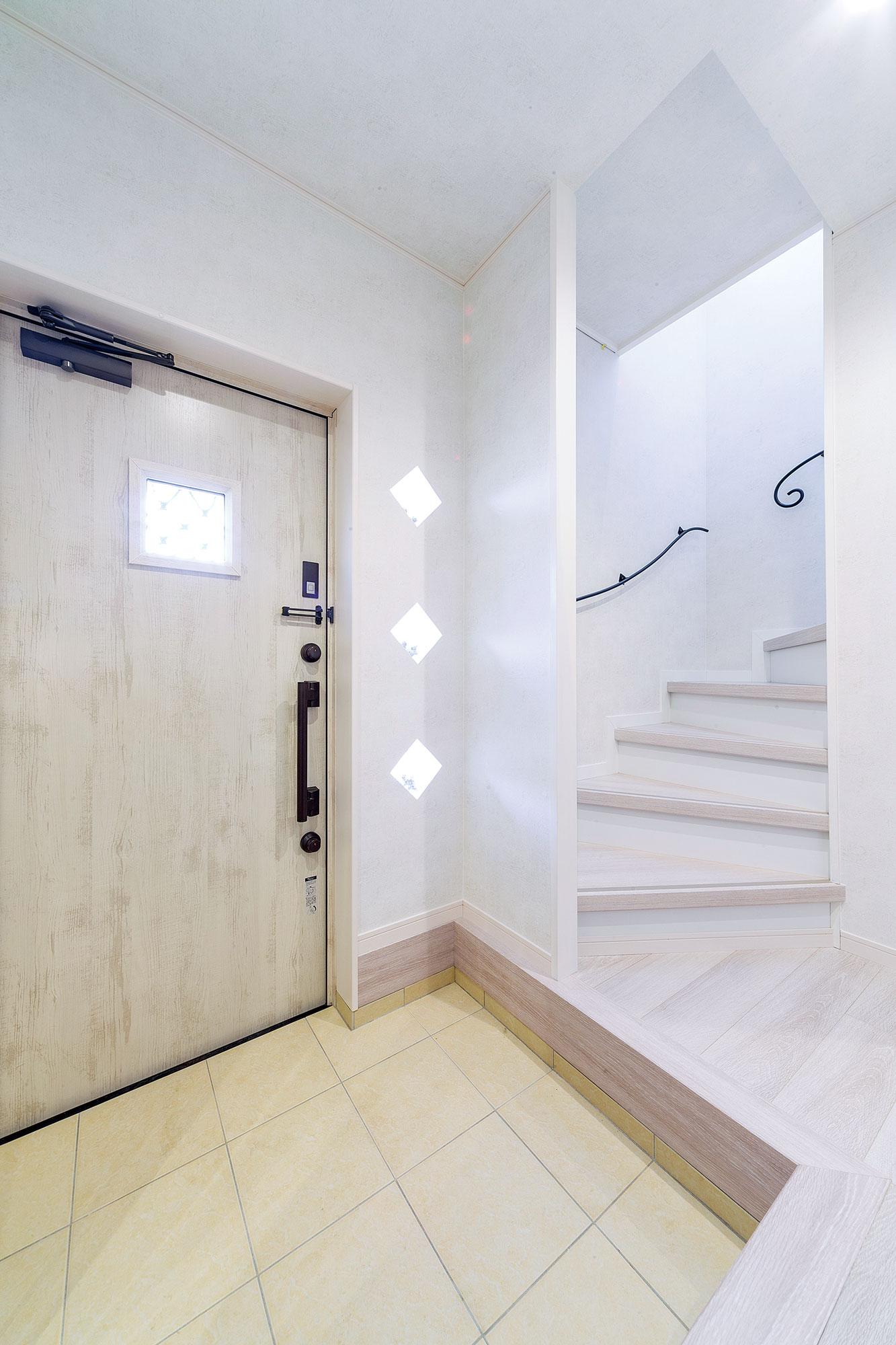 フレンチシャビー調の玄関戸、ロートアイアンの手すりなど、爽やかな印象の玄関