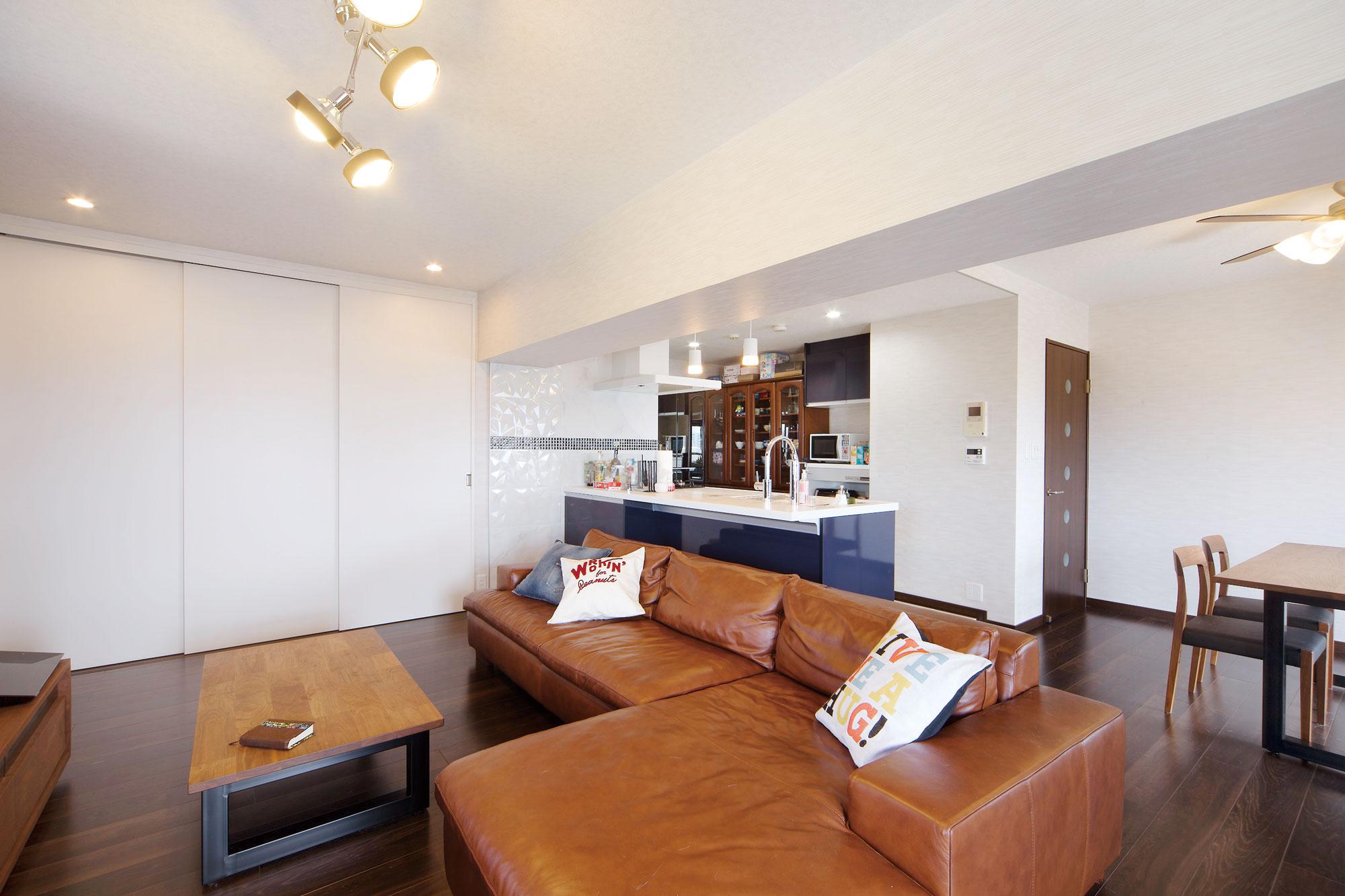 レザー張りのソファでゲストにはくつろぎの雰囲気を。使い勝手を考えて三連引戸の収納も設置。