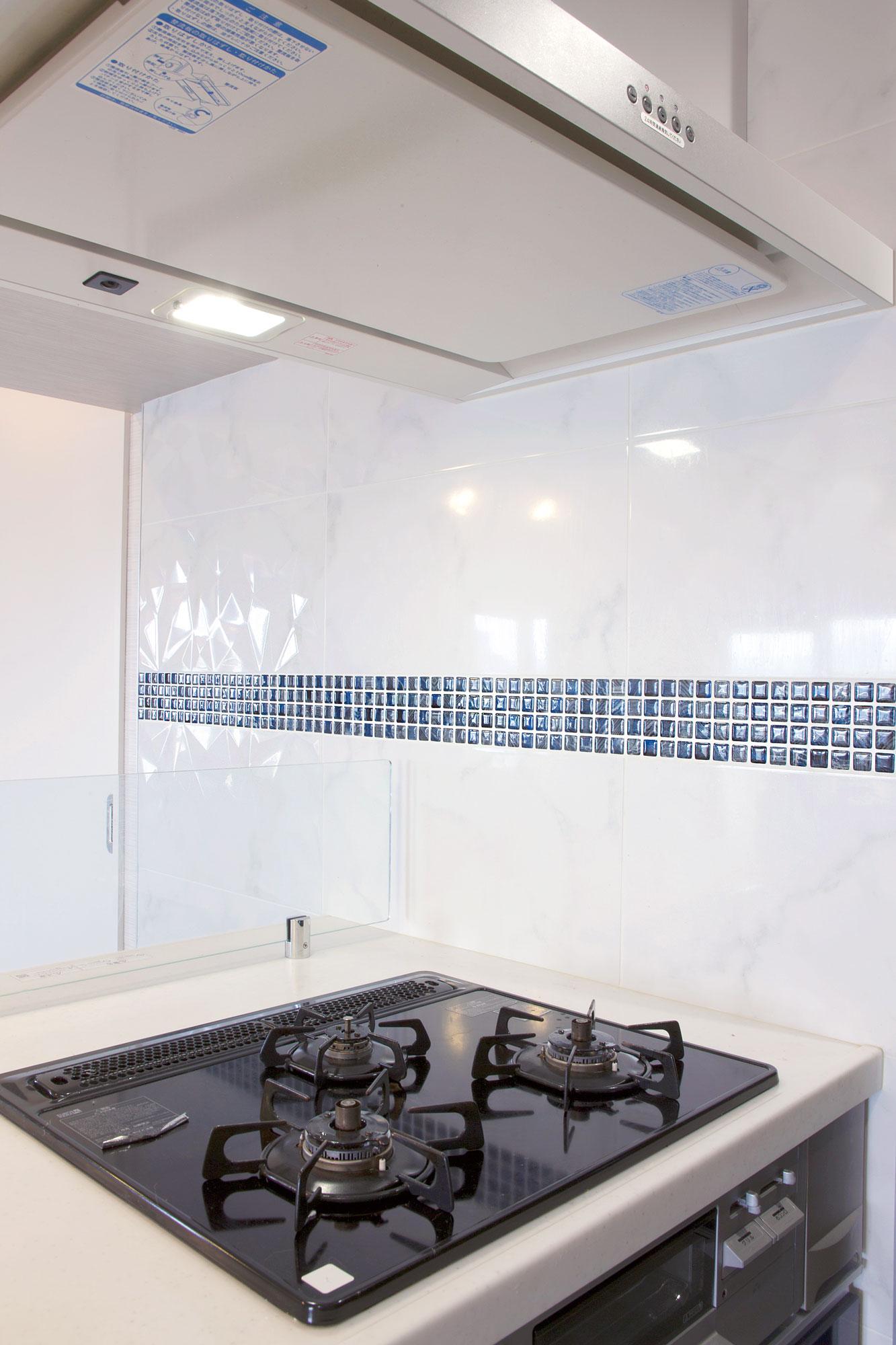 白いキッチンパネルには、凹凸が光に反射するモザイクタイルをアクセントに。
