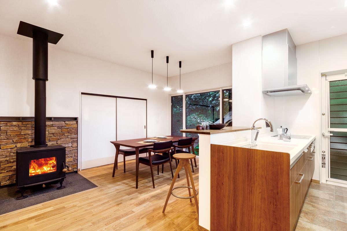 床はタモの無垢材。木目調のキッチンと薪ストーブが引き立てあいます。