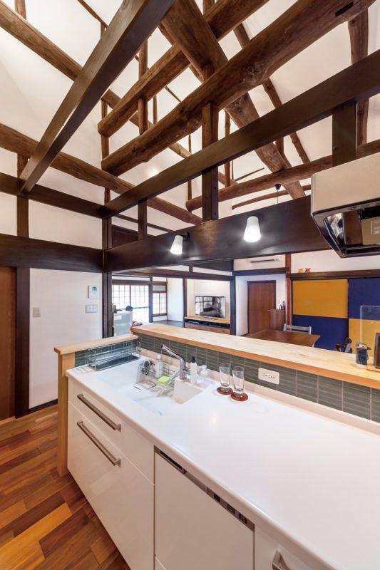 丸太梁をのぞむ吹き抜けのオープンキッチン