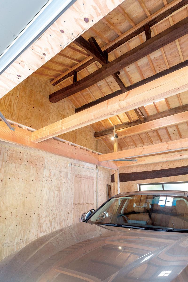 かつては牛小屋だったスペースはピットスペース兼ガレージに。新旧の構造材が支えています。