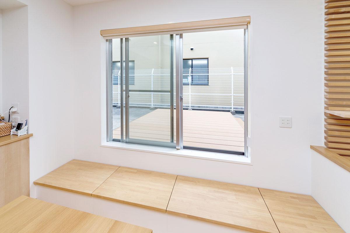 ダイニング横の窓から出入りできるウッドデッキを設置。ステップ台はベンチ兼収納スペースにして有効活用