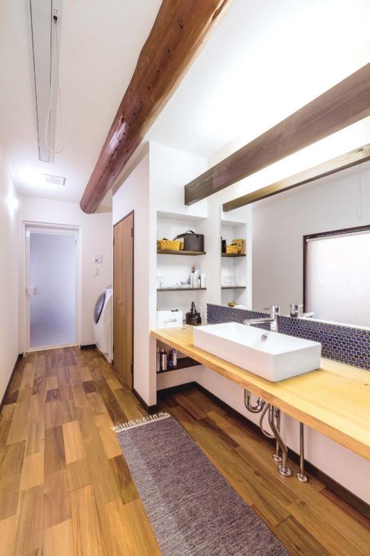 梁を活かした洗面脱衣室。洗面台壁面に貼られた名古屋モザイク工業の青いタイルがアクセントになっています。