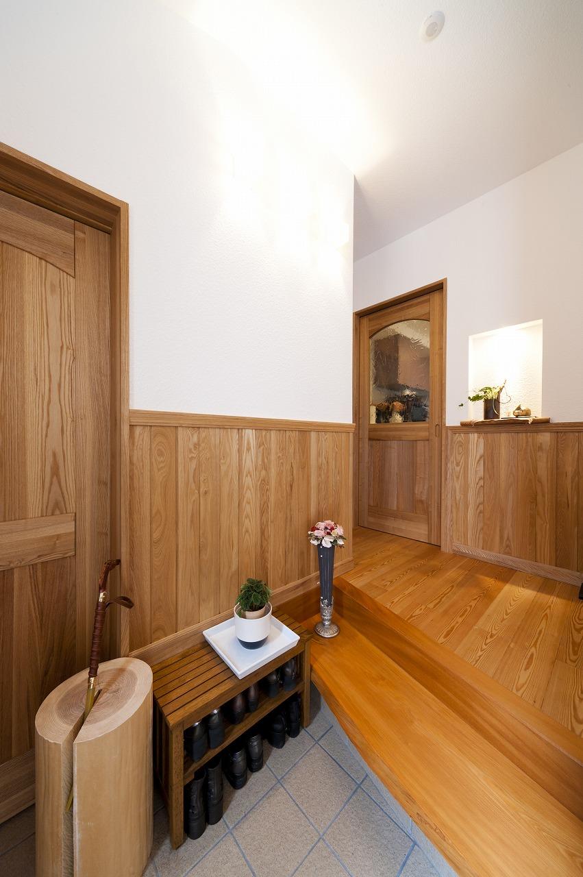 玄関の床はナラ無垢材、腰壁はタモ材、凹凸のあるウッドチップクロスの上を漆喰塗りしています。