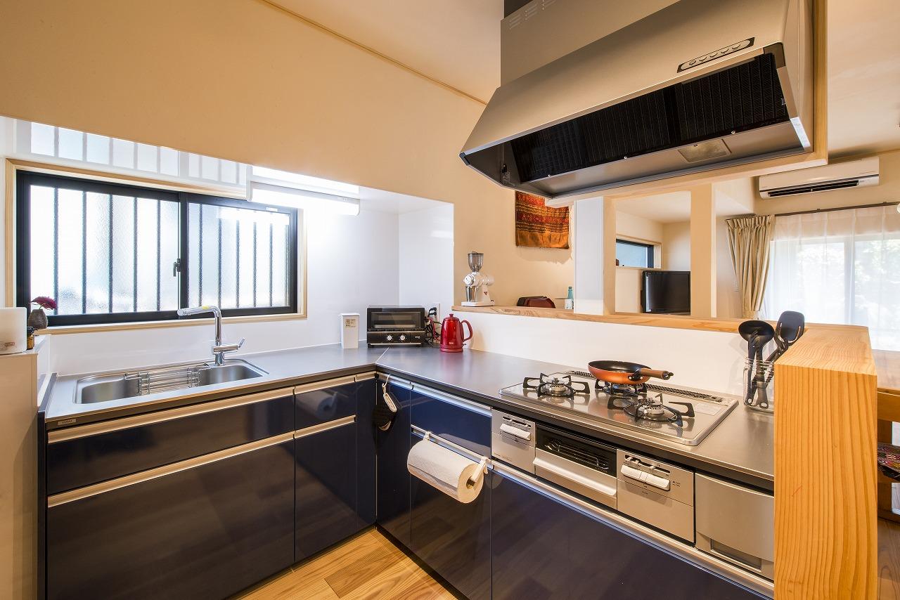 部屋が狭くなるのを避けるためにL字型にしたキッチン。窓際は梁で換気扇の設置が難しくダイニング面に設置しました。