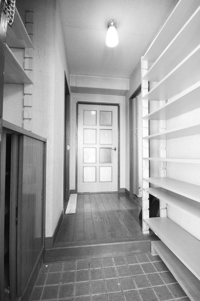 傷みが見られた玄関。右側と下駄箱上部の棚は収納が足りないためDIYで作ったもの。