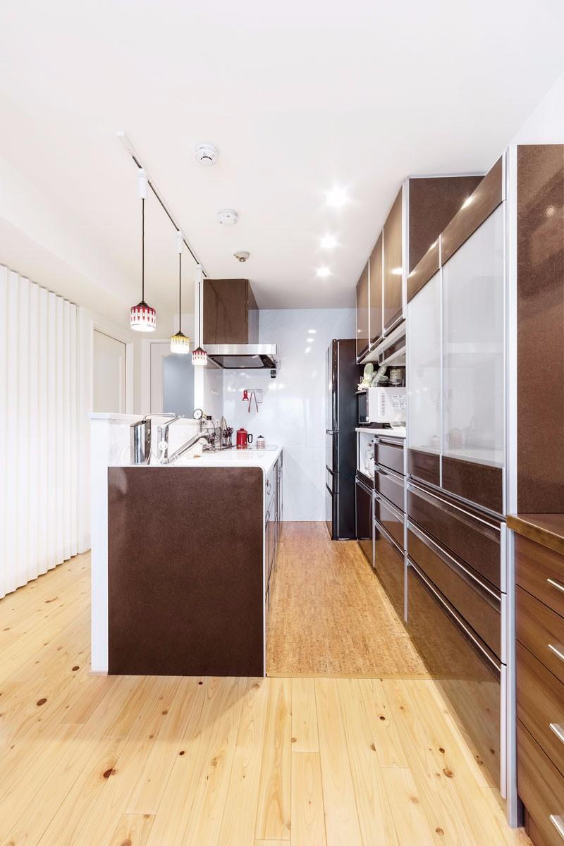 システムキッチンとカップボードは茶色で統一。床は汚れに強いセラミックのコルクタイルを