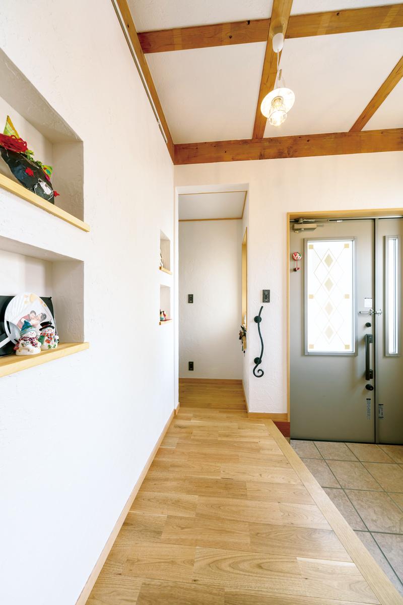 玄関はクルミの床材と白い漆喰壁で優しい雰囲気に。